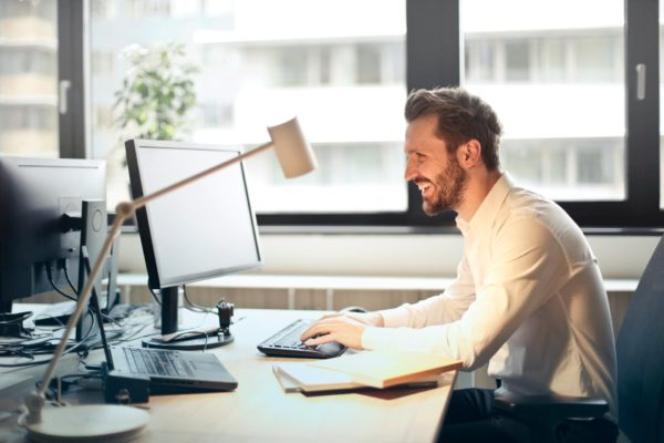 A happy man working on a computer in the office